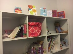 Bookshelf with cards, books, dolls, and legos.